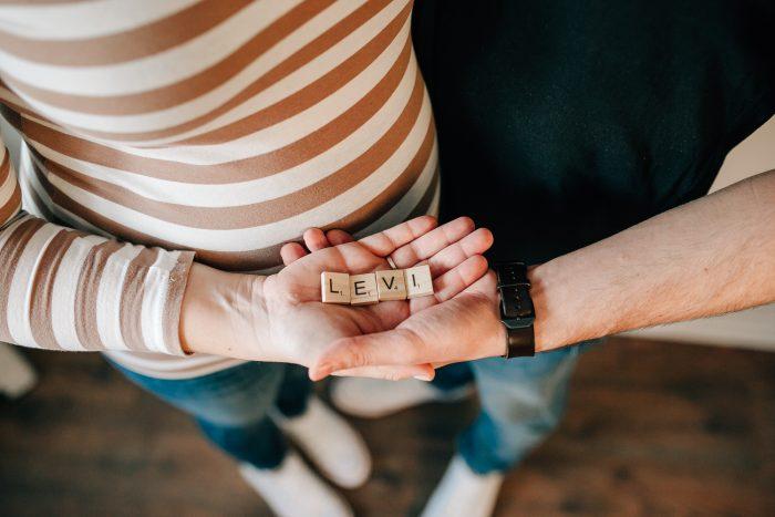 Scrabble Buchstaben auf Händen der werdenden Eltern