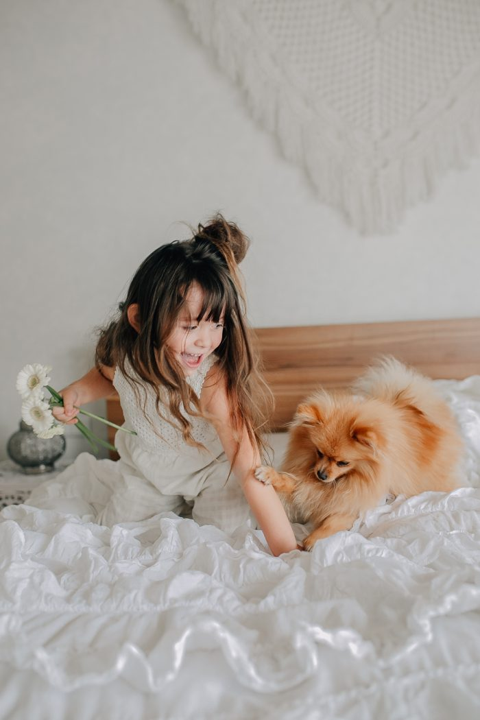 Mädchen mit Hund und Blumen in der Hand