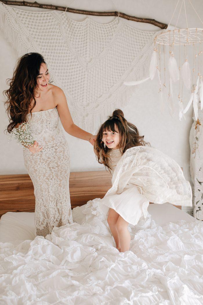 Mama und Tochter springen auf dem Bett mit Makramee und Traumfänger an der Wand