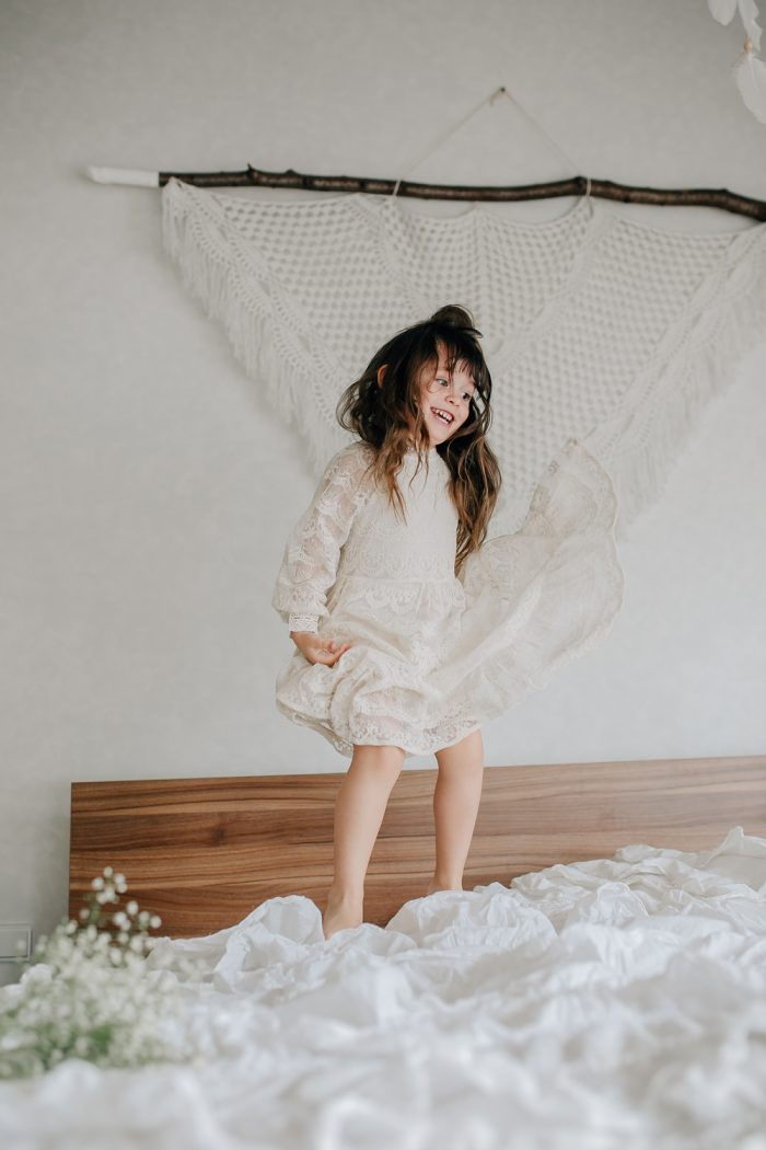 Mädchen springt auf Bett