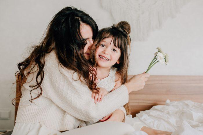 Mama und Tochter kuscheln gemeinsam auf dem Bett