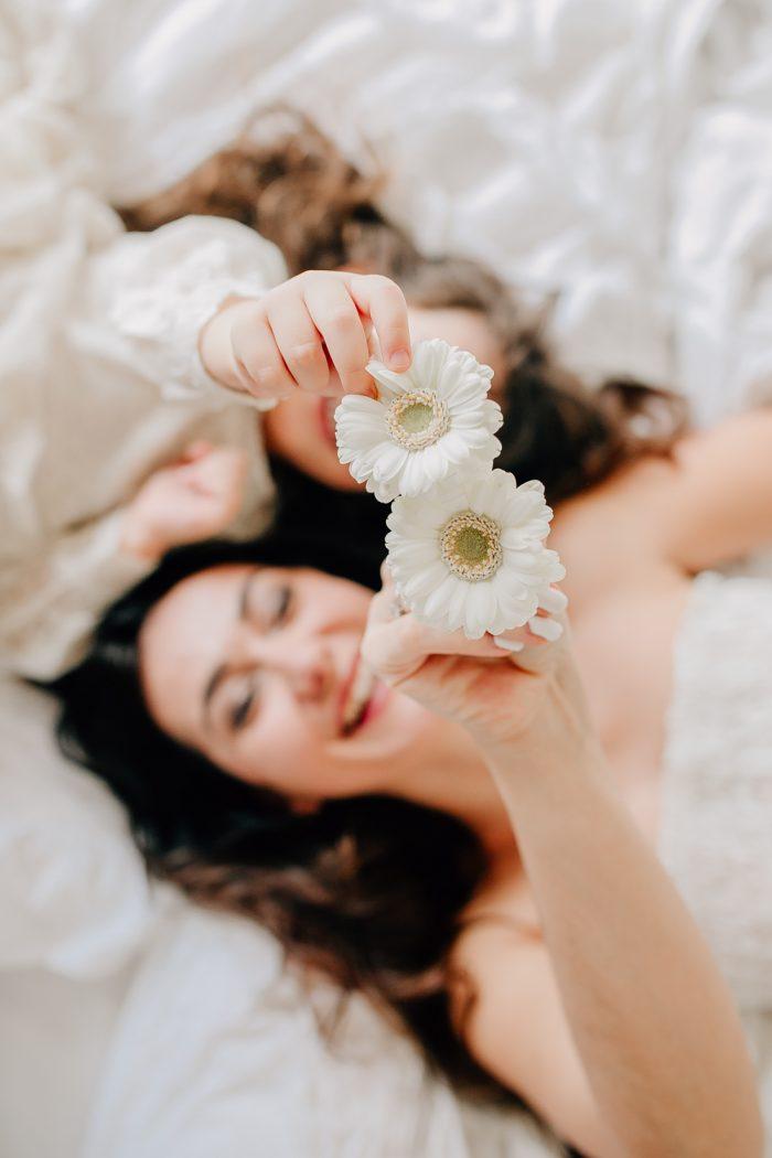 Mama und Tochter halten Blumen in die Kamera