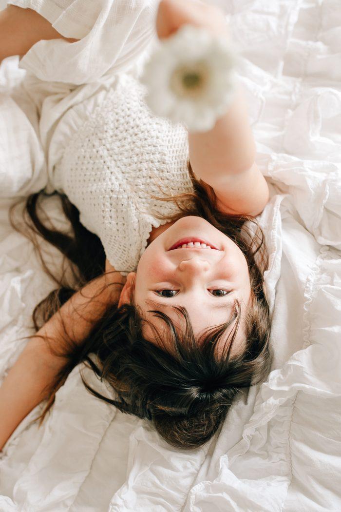Mädchen lacht in Kamera und hält weiße Blume in die Kamera