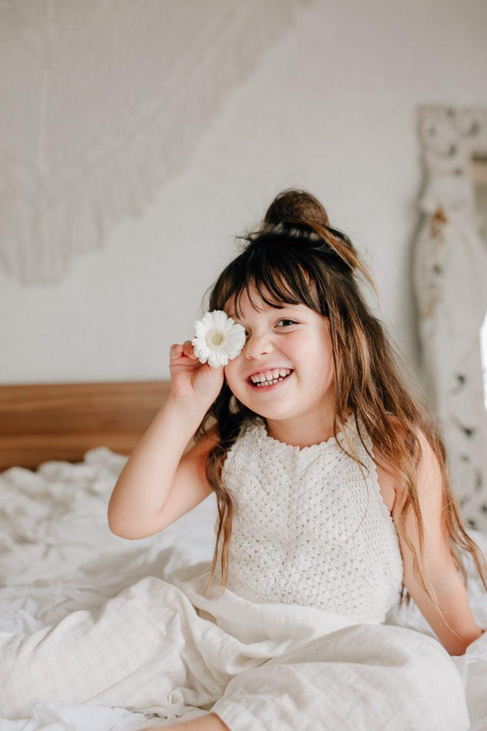 Mädchen mit weißer Blume vor Auge lacht in Kamera