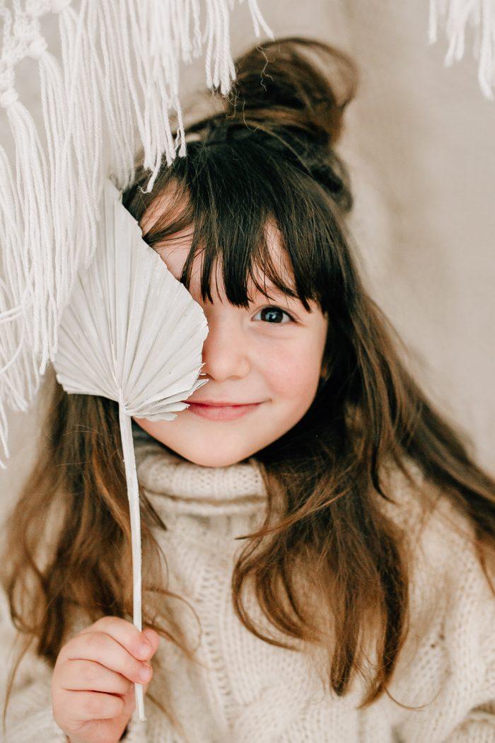 Mädchen mit Blumendeko vor dem Auge
