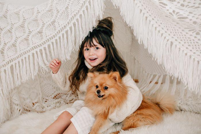 Mädchen mit Hund im Arm sitzt in gehäkeltem Tipi zelt